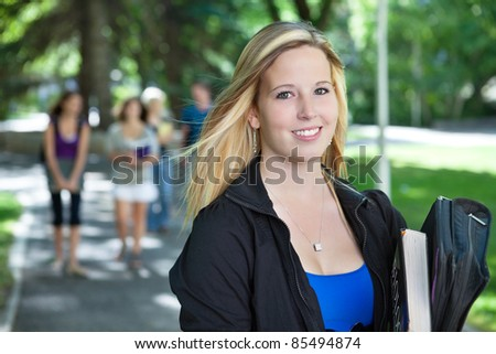 Portrait of young girl smiling with her classmates walking in the background - stock photo