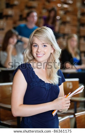 Portrait of young girl standing in auditorium with classmates in background - stock photo