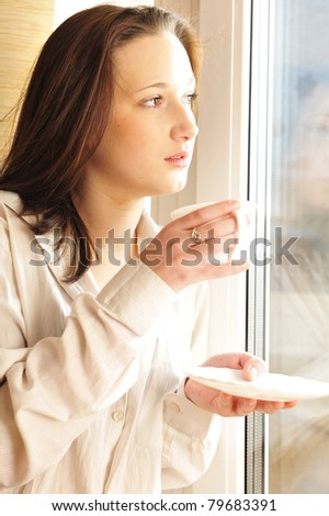 Portrait of young girl standing near a window at home. Drinking coffee and warming in sunbeam - stock photo