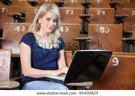 Portrait of young girl using laptop in lecture theatre - stock photo