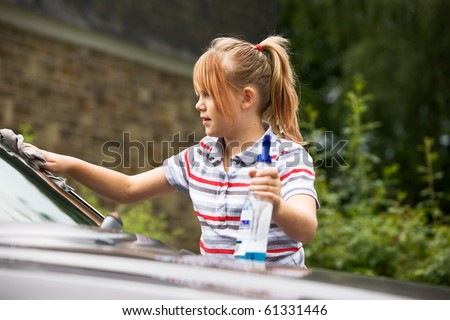 Portrait of young girl washing car - stock photo