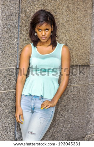 Portrait of Young Girl. Wearing a green tank top, fashionable jeans, drop earrings, a young pretty black woman is standing against the wall, lowering her forehead, intensely looking at you. - stock photo