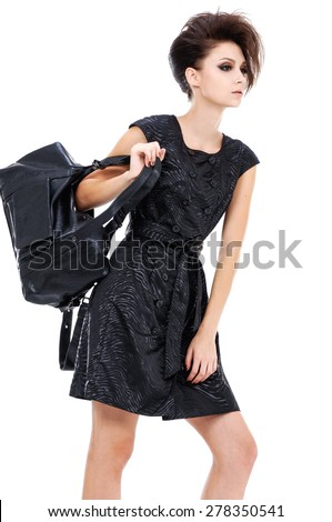 Portrait of young girl wearing black dress posing in studio - stock photo