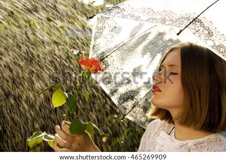 Portrait of young girl with a rose under the umbrella. Rainy weather.