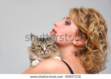 Portrait of young girl with cat over gray - stock photo