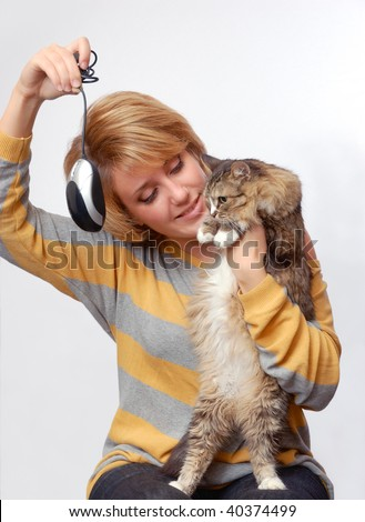 Portrait of young girl with cat over grey background - stock photo