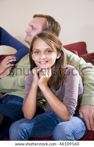 Portrait of young girl with father sitting at home on sofa - stock photo