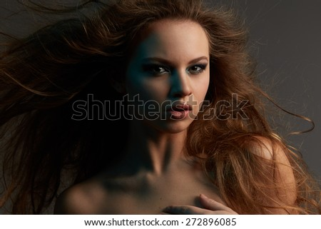 Portrait of young girl with long hair on grey background - stock photo