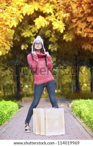 Portrait of young girl with shopping bag posing in autumn park. shot outdoor during autumn