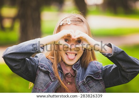 Portrait of young girl with tongue out  having fun outside. Funny kid looking cheerfully at camera through heart made by hands. Horizontal color photo. - stock photo