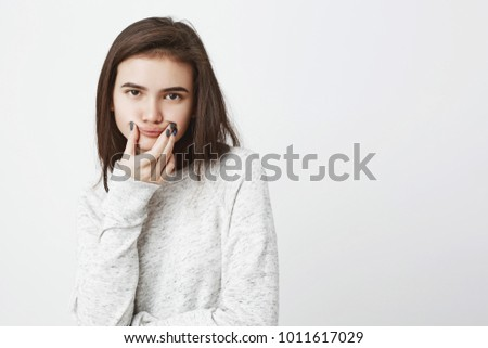 Portrait of young gloomy teenager expressing dissatisfaction holding mouth with hands to imitate smile while standing over white background. Girl expresses her opinion about boring film she watched