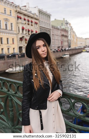 Portrait of young gorgeous brunette women with long hair standing on a river bridge in cloudy autumn day, stylish female tourist resting after active walking in city with beautiful architecture - stock photo