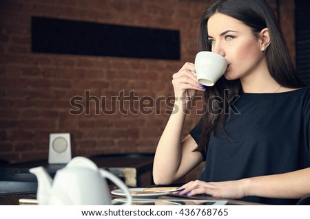 Portrait of young gorgeous girl drinking tea and thoughtfully looking out of the coffee shop window while enjoying her leisure time alone. Student has lunch in cafe. - stock photo
