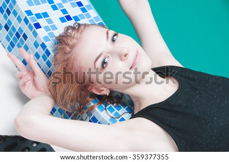Portrait of young gorgeous woman posing in a swimming pool
