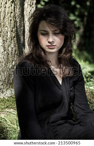 Portrait of young grieving woman in black - stock photo