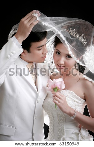 Portrait of young groom trying to kiss his bride - stock photo