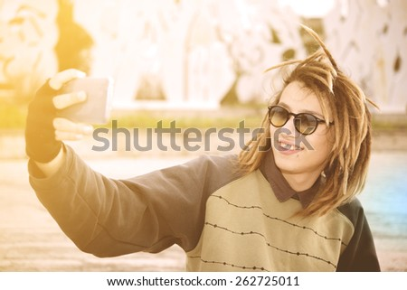 portrait of young guy outdoor with rasta hair smiling with smart phone in a lifestyle concept with a warm filter applied - stock photo
