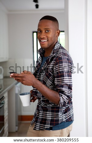 Portrait of young guy standing in the kitchen holding mobile phone and cup of coffee