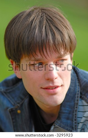 portrait of  young guy which looks aside on a green background - stock photo