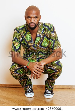 portrait of young handsome african man wearing bright green national costume smiling gesturing - stock photo