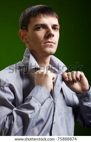 portrait of young handsome brunet guy in gray shirt checking collar on green