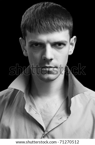 portrait of young handsome brunet guy posing in gray shirt on green