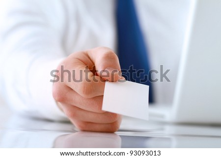 Portrait of young handsome business man holding blank white business card - stock photo