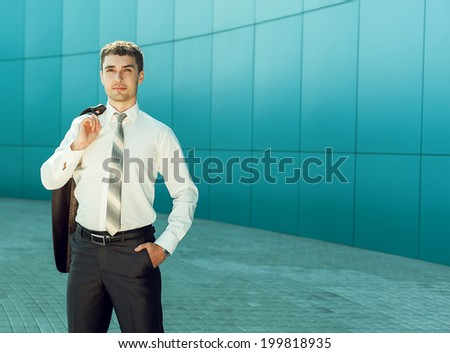 Portrait of young handsome business man near blue wall of business center looking up to the future. copy-space. Outdoor shot - stock photo