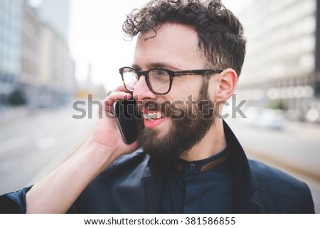 Portrait of young handsome caucasian bearded man talking smartphone, overlooking smiling - happiness, carefree, communication concept