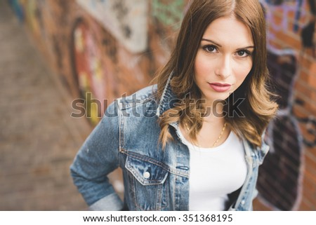 Portrait of young handsome caucasian blonde straight hair woman looking in camera, serious, wearing white shirt and jeans jacket - thinking future, pensive concept - stock photo