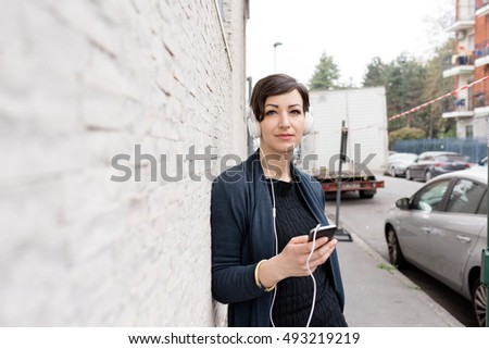 Portrait of young handsome caucasian brown hair woman leaning against a wall, listening music with headphones looking at camera - serene, enjoying, music concept