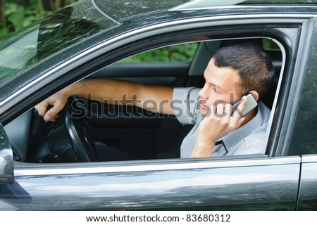 Portrait of young handsome dark-haired man driving car and speaking on mobile phone. - stock photo