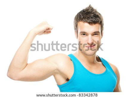 Portrait of young handsome dark-haired man wearing blue t-shirt, holding his arm up to show how strong he is against white background.