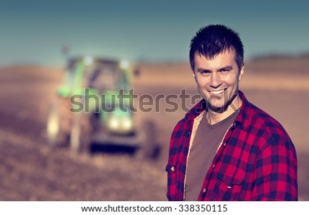 Portrait of young handsome farmer on farmland. Tractor working in background - stock photo