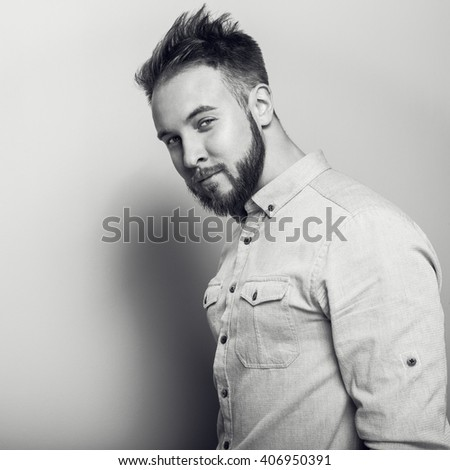 Portrait of young handsome friendly man in bright shirt. Black-white studio photo on light grey background. - stock photo