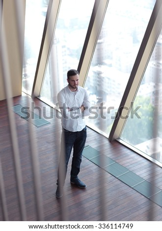 portrait of young handsome hipster business man with beard at modern office space interior - stock photo