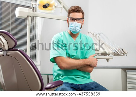 Portrait of young handsome male doctor in green costume wearing medical mask and glasses sitting in dentist chair in dental clinic with hands crossed. Face expressions, emotion, health care, medicine. - stock photo