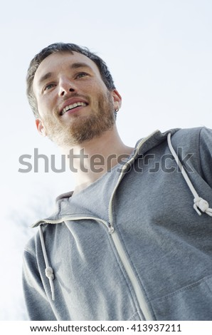Portrait of young handsome man against blue sky in sunlight - stock photo