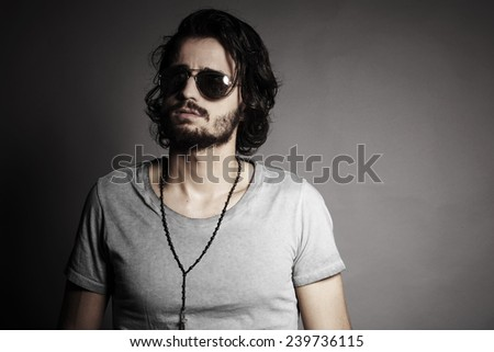 Portrait of young handsome man, against grey background - stock photo