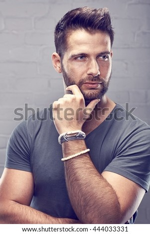 Portrait of young handsome man against white brickwall. - stock photo