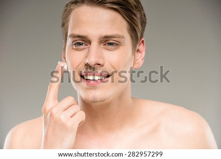 Portrait of young handsome man applying cream lotion on face. - stock photo