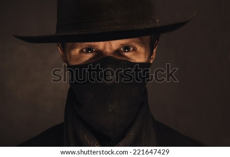 Portrait of young handsome man cowboy in a black hat and scarf - stock photo