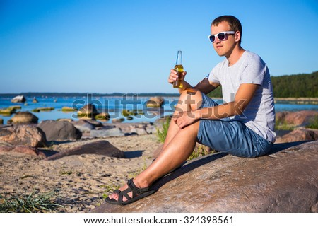 portrait of young handsome man drinking beer on stony beach - stock photo