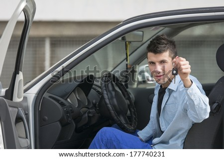 Portrait of young handsome man driving car