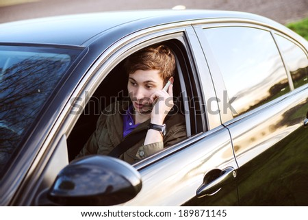 Portrait of young handsome man driving car and speaking on mobile phone