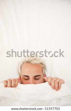 Portrait of young handsome man in bed - stock photo