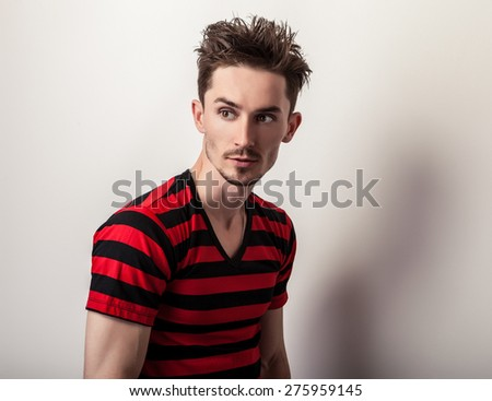 Portrait of young handsome man in red-black t-shirt. - stock photo