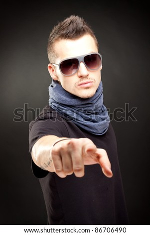 portrait of young handsome man in sunglasses pointing to the camera - stock photo