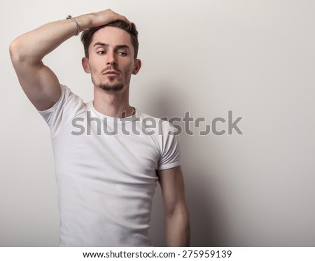 Portrait of young handsome man in white t-shirt. - stock photo