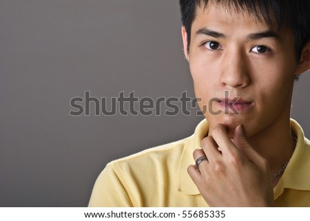 Portrait of young handsome man of Asian thinking and watching. - stock photo